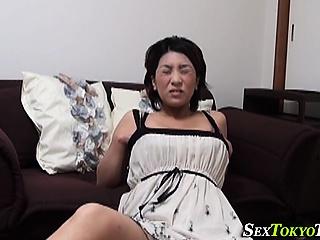 Japanese milf rubs pussy